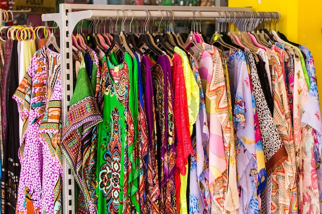 Different on hangers close up. colorful women's dresses on hangers in a retail shop