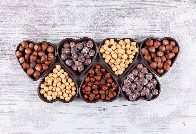 Different hazelnuts in a line up heart shaped bowls on a white wooden table. top view.