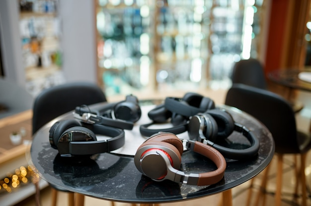 Different headphones on the counter in speaker system store, nobody. audio shop choice, showcase with earphones, multimedia store assortment
