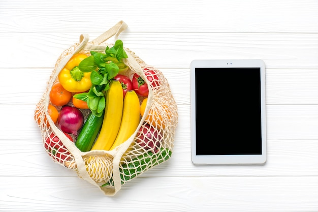 Different health food - yellow bell pepper, tomatoes, bananas, lettuce, green, cucumber, onions in mesh bag tablet with black touch screen on white wooden background