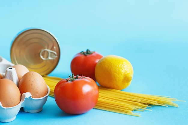 Different healthy food products on a blue background. top view. fruit, vegetable, eggs and grocery online shop.