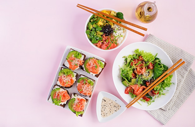 Different healthy salads and salmon sandwiches