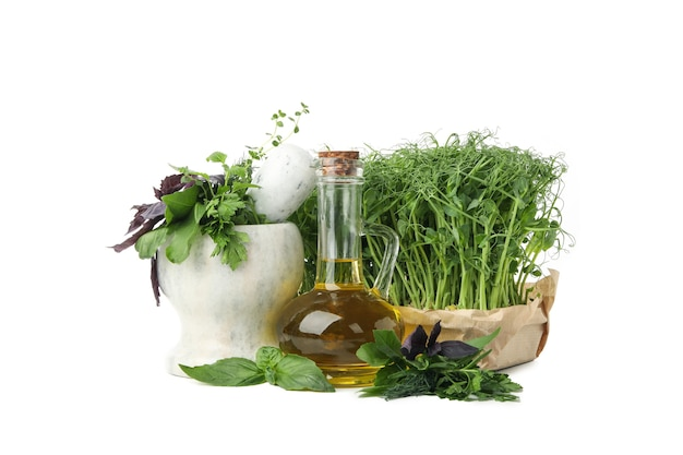Different herbs, oil and marble mortar isolated on white background