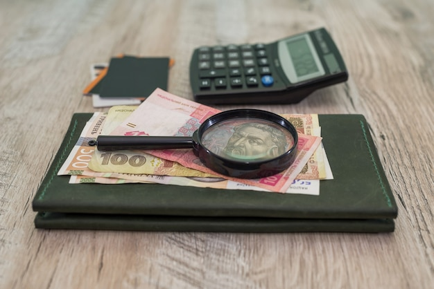 나무 테이블에 다른 hryvnia, 신용 카드, 지갑, 계산기, 돋보기. 금융 개념.