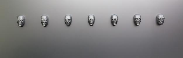 Различные человеческие эмоции, скульптурная маска на стене, вид спереди. концепция эмоций, модели лица