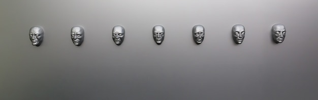 Different human emotions, sculptural mask on the wall, front view. emotion concept, face models