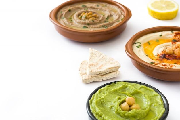Different hummus bowls chickpea hummus, avocado hummus and lentils hummus isolated on white