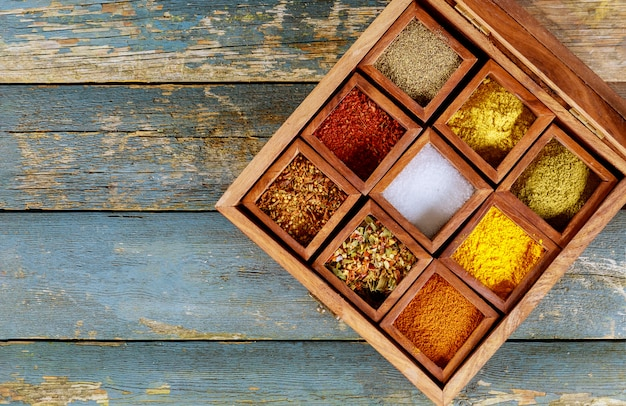 Different indian spices in wooden boxes on old wooden background