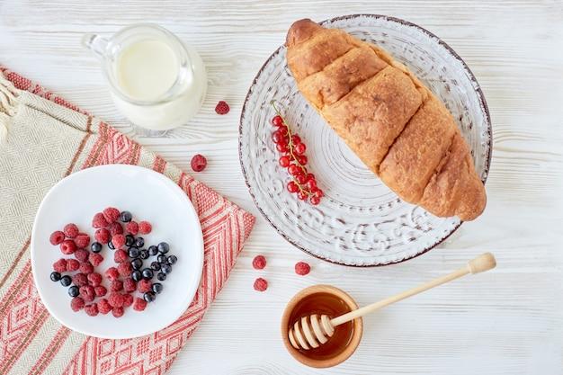 朝食のさまざまな食材。木板、果実、コーヒー、牛乳、蜂蜜、白いテーブルクロスの上のプレートにクロワッサン。伝統的なフランスの朝食。上面図