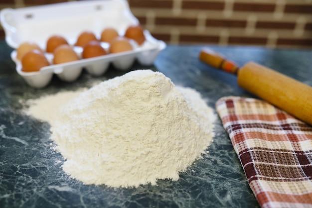 台所のテーブルで小麦粉製品を準備するためのさまざまな材料