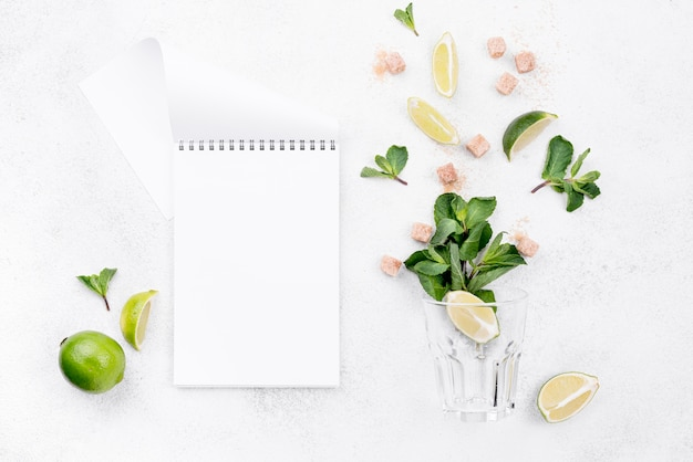 Different ingredients on white background with empty notepad