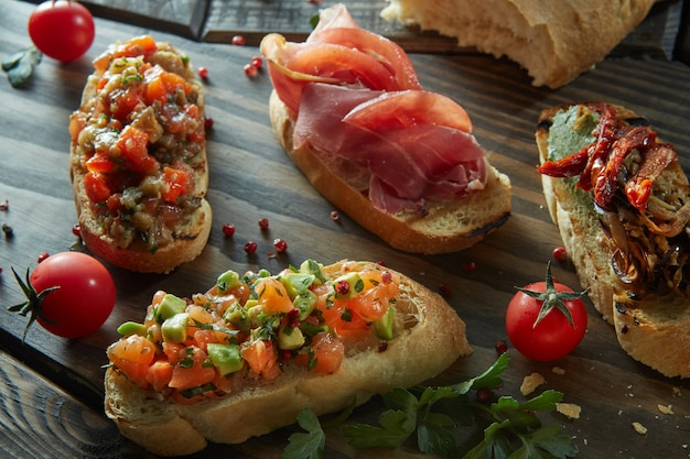 Различные итальянские закуски для вина на деревянном темном столе.