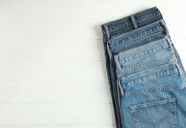 白い木製の背景、テキスト用のスペースに折り畳まれた別のジーンズ