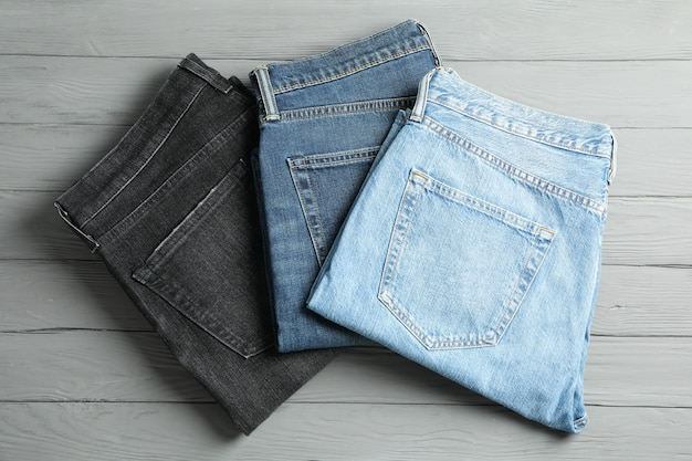 Different jeans on grey wooden table