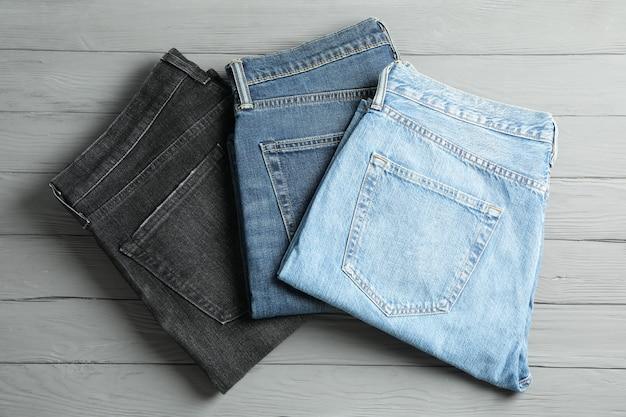 灰色の木製のテーブルに別のジーンズ