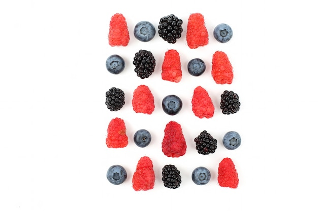 Different juicy berries laid out in a square on a white