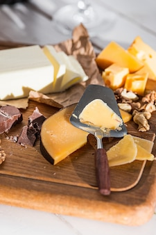 The different kind of cheese and walnuts on wooden background