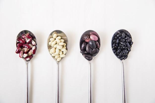 スプーンの中の異なる種類のインゲン豆。白い表面。上面図