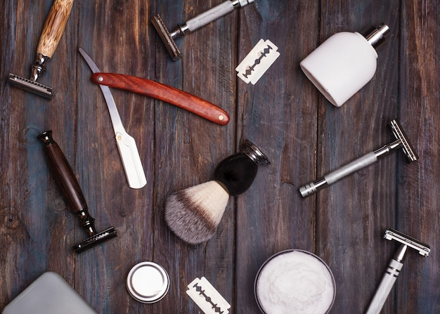 Different kind of razors including safety and straight, blade, brush and perfume on a wooden background