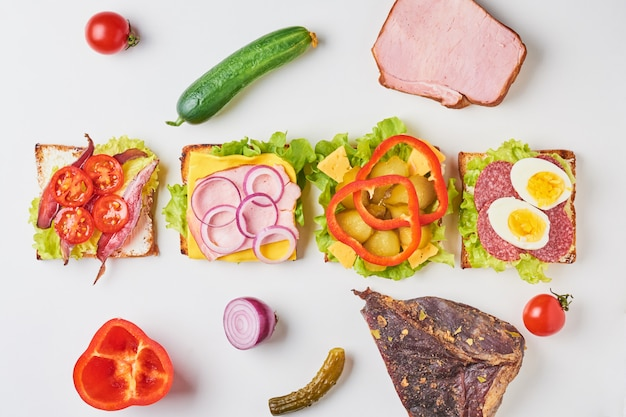 Different kind of sandwich and ingredients on a white background, top view