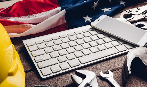 Different kind wrenches with american flag and smartphone blank screen on keyboard