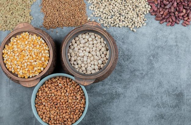 Diversi tipi di semi di fagioli, lenticchie, piselli in piatti sul nero.