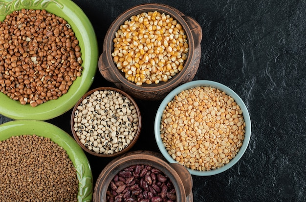 Different kinds of bean seeds, lentil, peas in dishes on black .