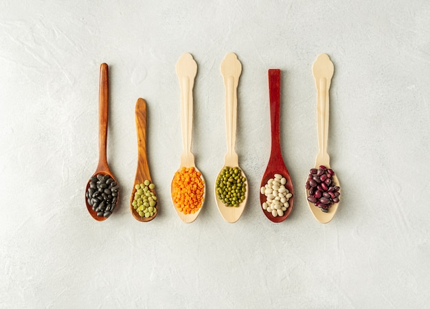 Different kinds of beans in spoons on white background