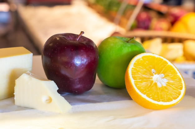 Different kinds of cheese with fresh fruits on table