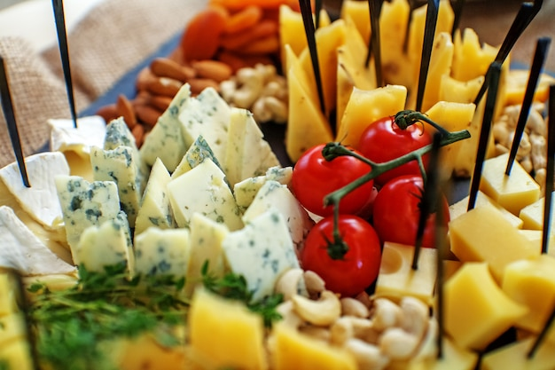 Different kinds of cheese with fruits, nuts and cherries.