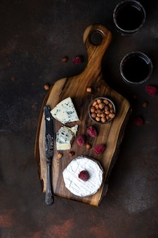 Different kinds of cheese on the wooden board with berries and wine