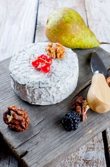Different kinds of cheeses on a white old wooden table.