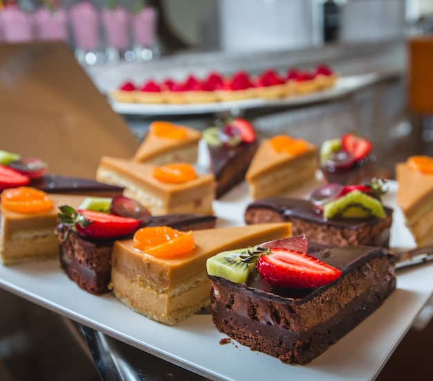 Different kinds of cream, caramel and chocolate cakes with fruits on the top
