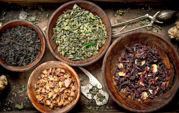 Different kinds of fragrant tea in bowls on a rustic background