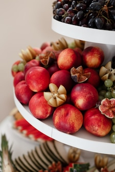 Different kinds of fresh fruit on a tray on a banquet. fruit wall with peaches, grapes and figs. selective focus