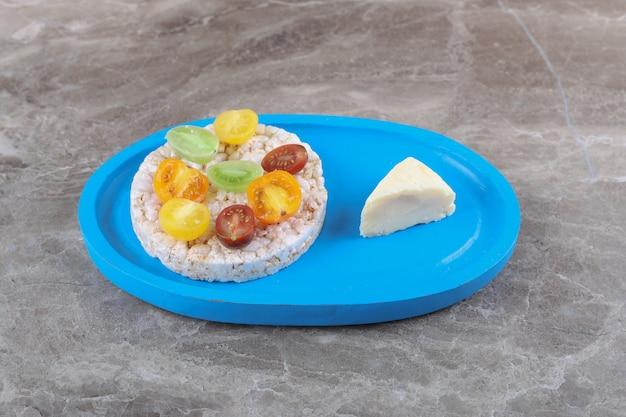 Diversi tipi di frutta sulle gallette di riso soffiato sul vassoio di legno, sulla superficie di marmo