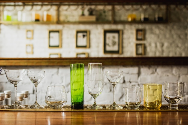 Different kinds of glasses on a bar counter, rocks, old fashioned, highball, nick and nora, coupe