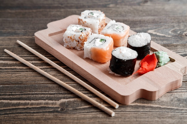 Different kinds of japanese rolls with wasabi and ginger on bamboo tray on wood