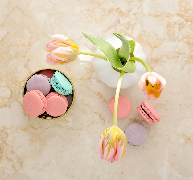 Different kinds of macaroons on marble and tulips