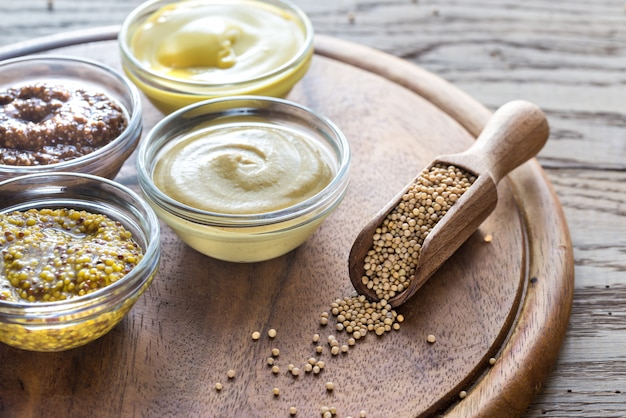 Different kinds of mustard on the wooden surface