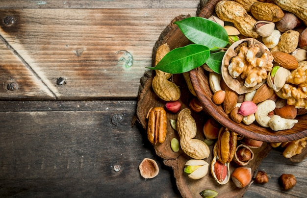 Different kinds of nuts in bowl with leaves.
