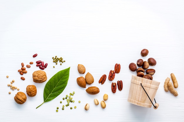 Different kinds of nuts set up on white wooden background with copy space.