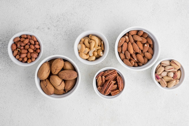 Different kinds of nuts in small and big white bowls