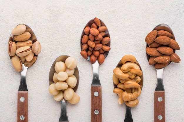 Different kinds of nuts in spoons top view