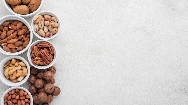 Different kinds of nuts in white bowls copy space