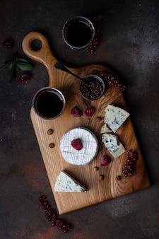ベリーとワインと木の板上のさまざまな種類のチーズ