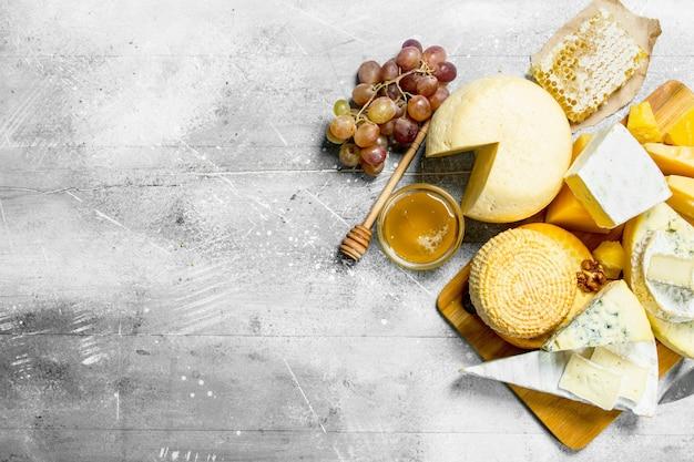 木製のテーブルに蜂蜜とブドウとさまざまな種類のチーズ。