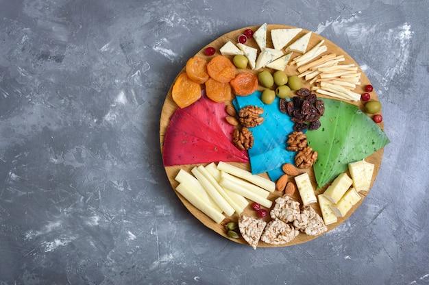 Различные виды сыров, кураги, цельнозернового хлеба, орехов, оливок, каперсов на деревянной доске. сырная доска, закуски. вид сверху
