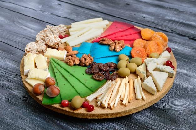 Различные виды сыров, кураги, цельнозернового хлеба, орехов, оливок, каперсов на деревянной доске. сырная доска, закуски.