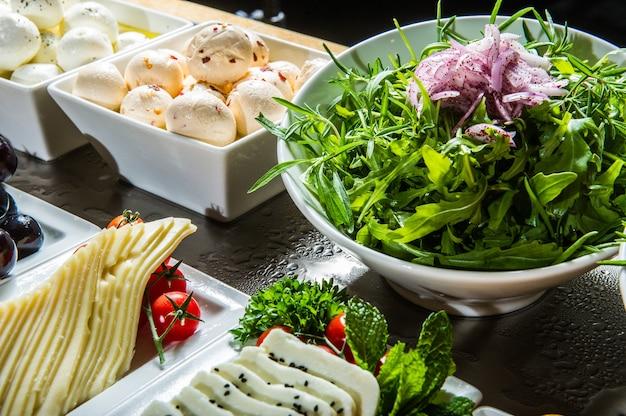 上から素朴な木製のテーブルでチーズ、ワイン、バゲット、フルーツ、スナックの種類。フランスのテイスティングパーティーやごちそうの風景。